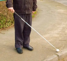 A recently blind man stands on the pavement outside Wye Surgery and learns how to cross the road with the aid of a white stick
