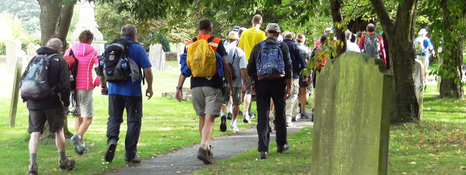 A large group of walkers on the North Downs Way National Trail passing through Wye churchyard on their way to Canterbury, via Dover
