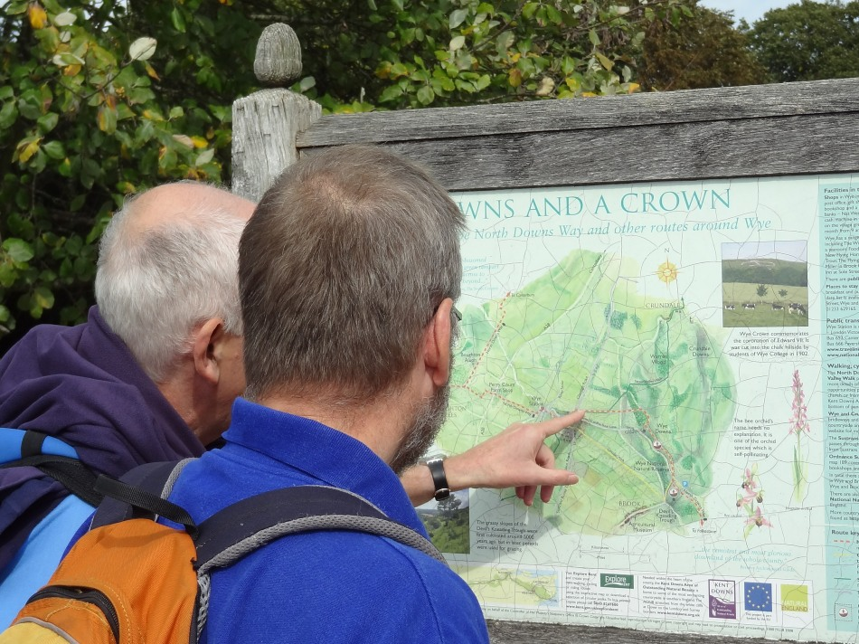 Two walkers on the North Downs Way National Trail consult the map in Wye churchyard