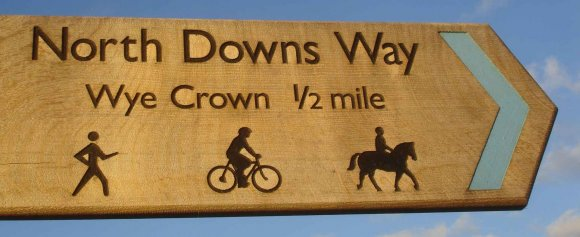 "North Downs Way National Trail. The oak signboard reads ""Wye Crown 1/2 mile"""