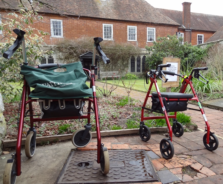 Four wheeled walkers parked side by side in the Latin School garden, while their owners visit the Wye Heritage Centre.