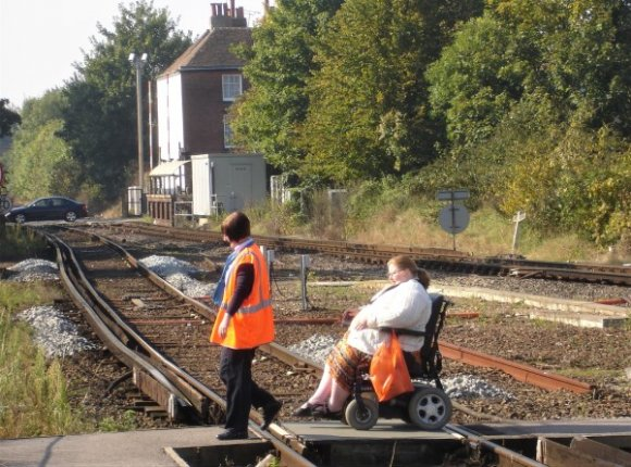 The at-grade crossing at Canterbury West Station. A wheelchair user is being guided over the rails by a station porter. Network Rail has replaced this crossing with a footbridge and lifts.